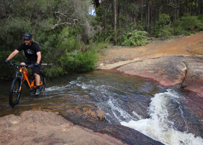 Cyclist on Giant E Mountain bike crossing a creek with water running through it on the Railway Heritage trail in John Forrest National Park.