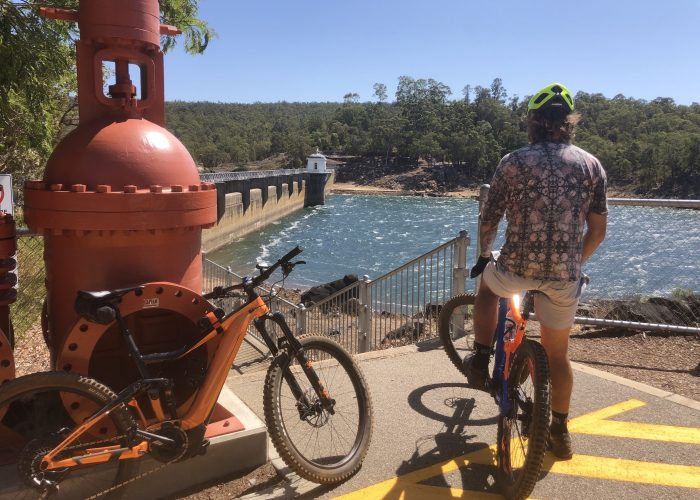 Cyclist sitting on a Giant E Mountain Bike looking over at the Mundaring Weir on a Perth Hills Mountain Bike Tour .