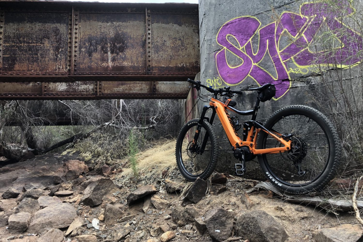 Giant E Mountain Bike below old rail bridge on Railway Heritage trail , graffiti on wall .