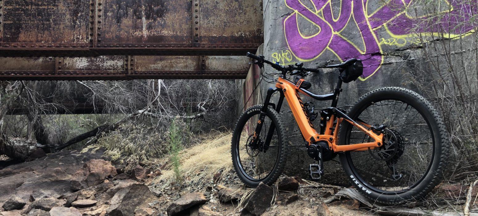 Giant E Mountain Bike below old rail bridge on Railway Heritage trail , graffiti on wall .