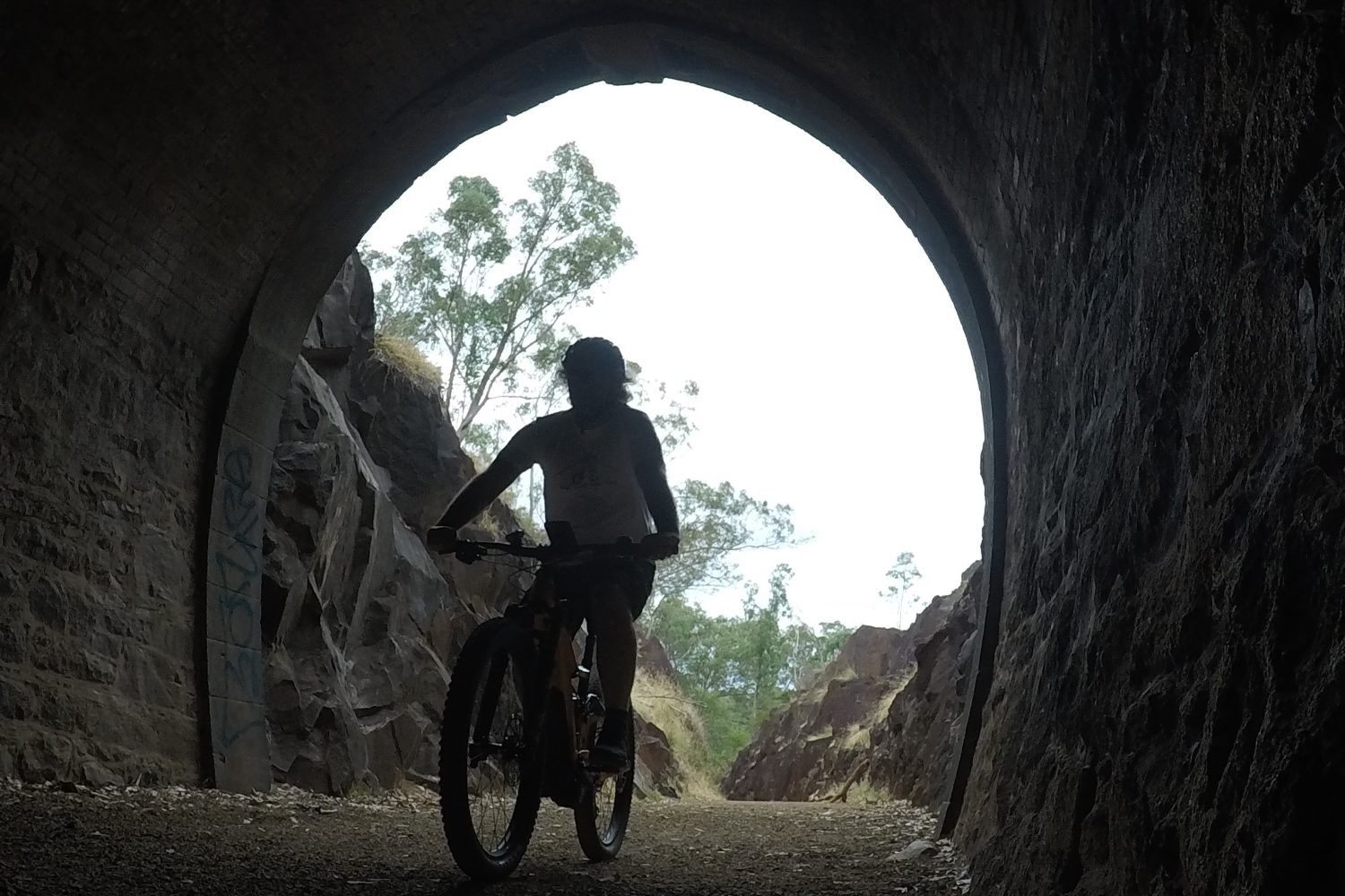 Cyclist Riding Giant E Mountain Bike into Swan View Tunnel in the John Forrest Nation Park on the Railway Heritage Trail on a Perth Hills Mountain Bike Tour.
