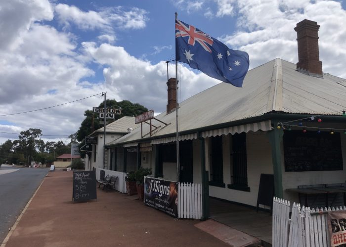 The original Chidlow Tavern with a large Australian flag flying from a flag pole on the roof on the original Sunday Session tour