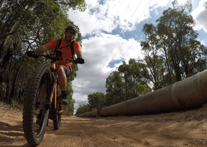 Cyclist on Giant E Mountain bike riding along KEP track near Mount Helena with CY Oconnor pipe line running along side of track