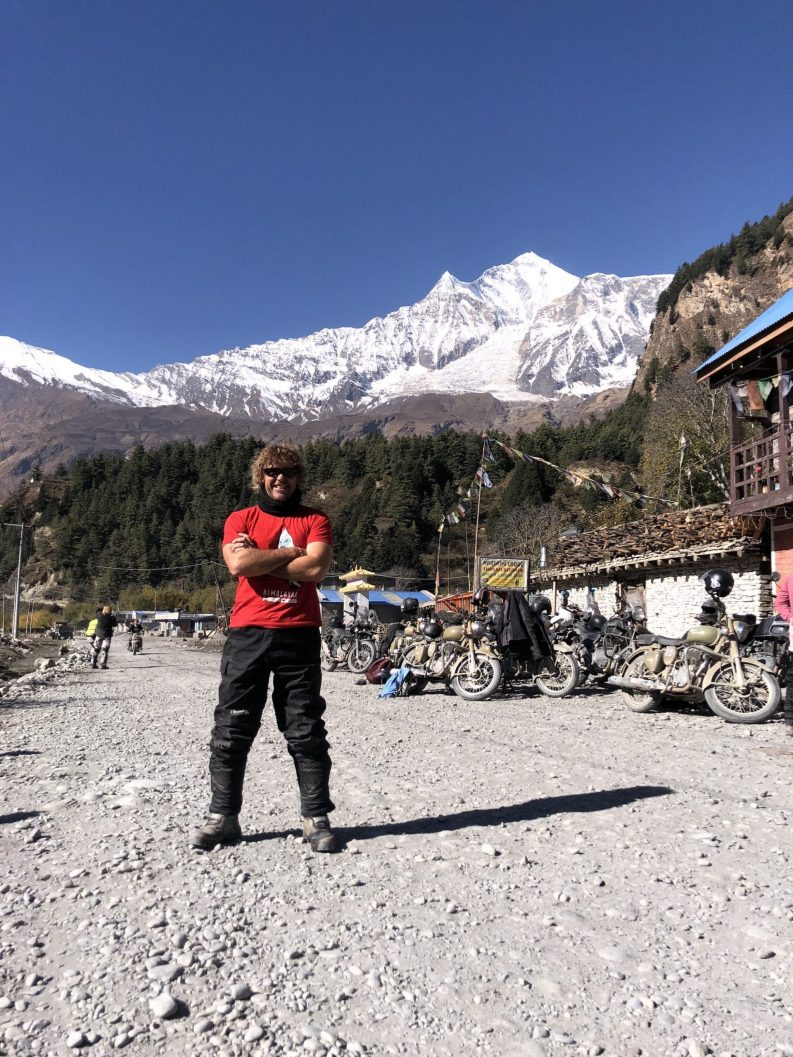 Business Owner Shayne Paton standing on a dirt road in Nepal with Himalayas mountain in back ground covered in snow