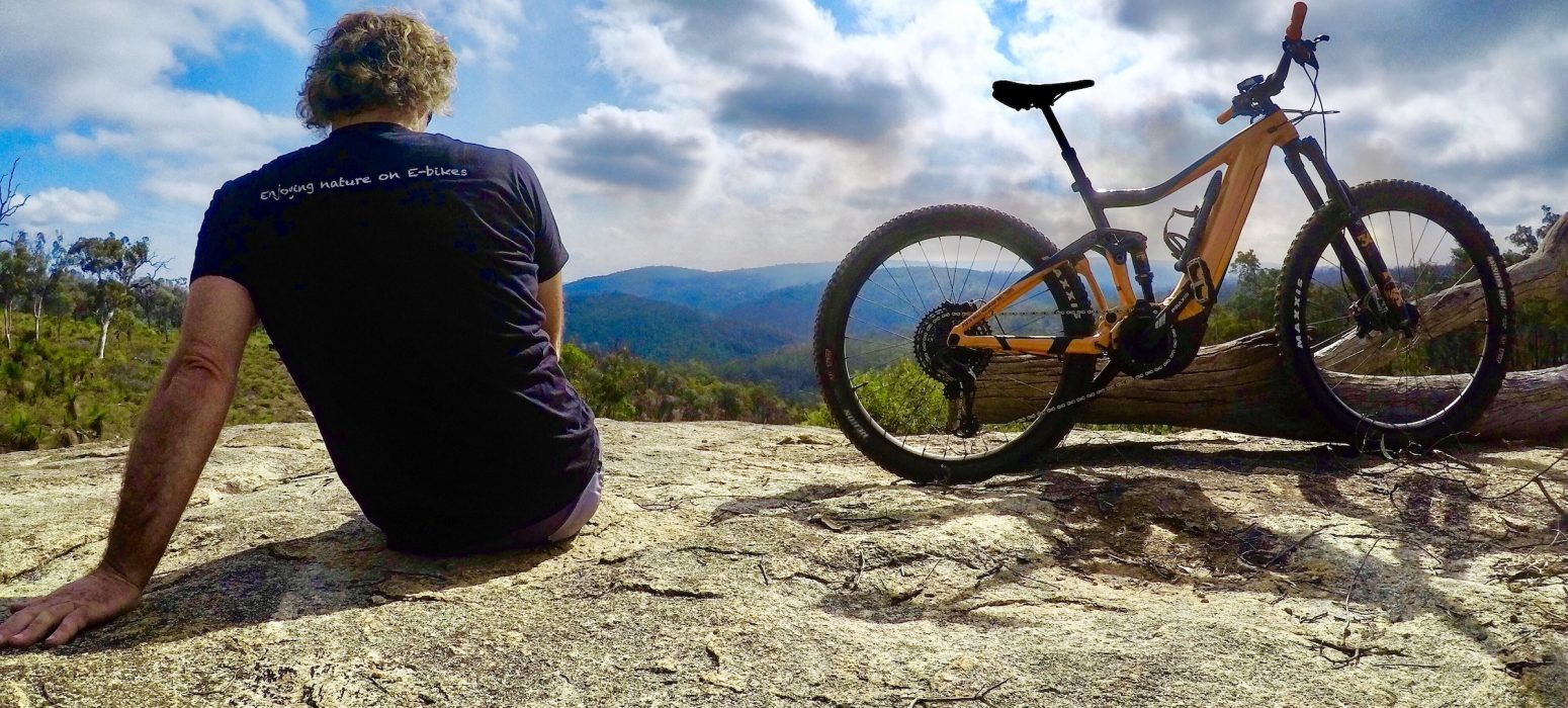 Cyclist sitting on rocky out crop with a Giant E mountain bike next to him , he is looking into the lower Helena Valley enjoying the tranquility of the bush.