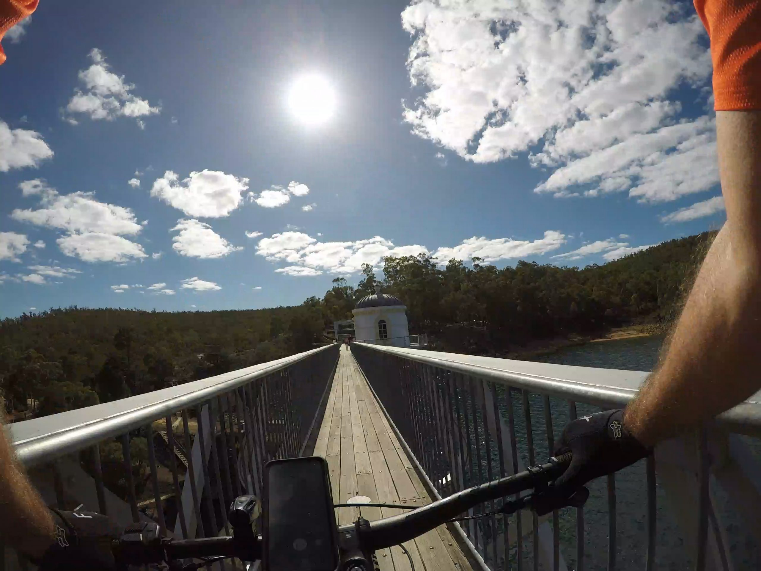 Cyclist on a Perth Hills mountain Bike tour crossing the Mundaring Weir , water on one side , dam wall on the other with blue Skys above.