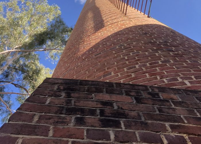 Looking up at the old brick chiminey at the original pump station 1 at the Mundaring Weir another stop on a Perth Hills Mountain Bike tour.