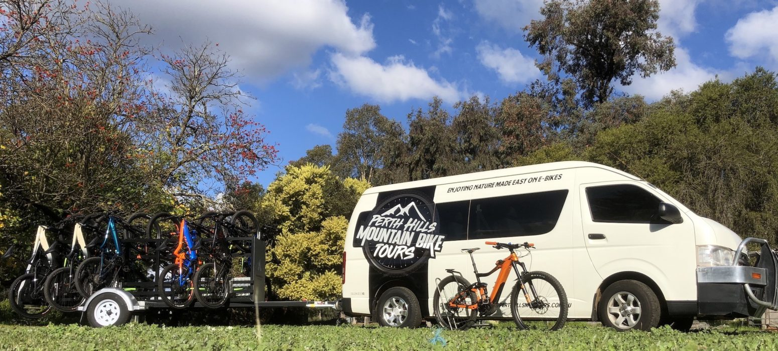 Perth Hills Mountain Bike Tours bus with large logo and the Perth Hills Mountain Bike Built Trailers with the GIANT E Bikes