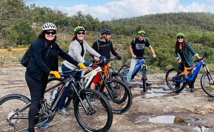Group of friends all sitting on the Giant E Bikes on a Tailor made Perth Hills Mountain Bike Tours , photo taken on Rock in John Forrest National Park.